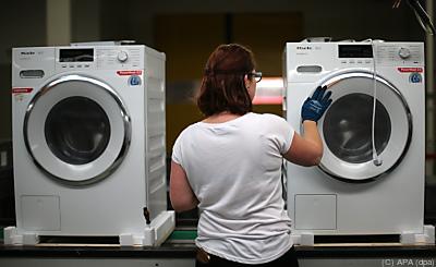 Eine Arbeiterin klebt Aufkleber auf eine Waschmaschine  - Wuppertal, APA (dpa)